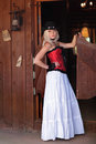 A girl with a wild west sexy woman in red corset and long white standing in the doorway of the old bar Stock Images