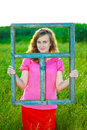 Girl and the window frame in grass that keeps thus showing absence of a house or roof Royalty Free Stock Image