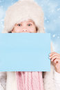 Girl in winter hat with blank board Royalty Free Stock Photography