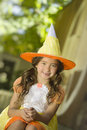 Girl in witch costume halloween a smiling toothless with brown eyes and long brown hair pigtails wears an orange yellow and white Royalty Free Stock Image