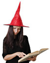 Girl with a witch hat portrait of teenager red reading spell book Stock Photos