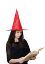Girl with a witch hat portrait of teenager red reading spell book Stock Photography