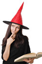 Girl with a witch hat portrait of teenager red reading spell book and thinking Royalty Free Stock Image