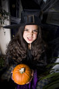 Girl in a witch's costume at a Hallowe'en party, holding a pumpkin Royalty Free Stock Photo
