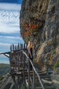 Girl on a wooden bridge standing at sunset the old that leads to the monastery Royalty Free Stock Image