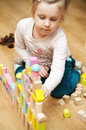 Girl with wooden toy blocks a four year old playing at home Stock Photography