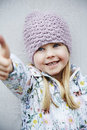 Girl in woolly hat cheerful and flowery coat Stock Photos