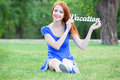 Girl with word vacation redhead in the park Royalty Free Stock Photography