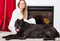 Girl wrapped in a blanket sits near the fireplace with dog Cane Corso Royalty Free Stock Photo