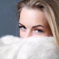 Girl wrapped in a fur coat on grey background Royalty Free Stock Photos
