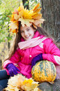 Girl in a wreath of maple leaves with pumpkin Stock Images