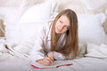 Girl writes diary lying bed morning Royalty Free Stock Photo