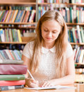 Girl writes essay in the library Royalty Free Stock Photo