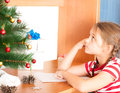 Girl writes a letter to santa claus little sitting at desk Royalty Free Stock Photo