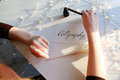 Girl writes pen fountain calligraphic letters, sitting at table Royalty Free Stock Photo