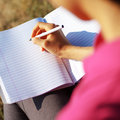 Girl Writing in Note Book Stock Photos