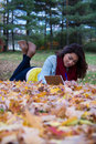 Girl writing in notebook while lying down on colorful autumn lea Royalty Free Stock Photo