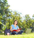 Girl writing in a notebook outdoors and looking at camera shot with tilt and shift lens Stock Images