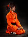The girl wushu in orange costume to meditate on dark background Stock Photo