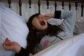 Girl yawning on bed Royalty Free Stock Photo