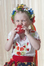 The girl of years eats red apple in a national ukrainian suit Stock Photos