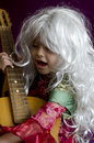 Girl years wig sings and plays guitar in the gypsy dress Royalty Free Stock Photo