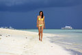 Girl in yellow bikini walking on the white beach under the storm sky Royalty Free Stock Photo