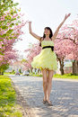 Girl in a yellow dress running down the avenue Royalty Free Stock Photography