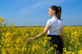 Girl in yellow flower field, beautiful spring landscape, bright sunny day, rapeseed Royalty Free Stock Photo