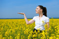 Girl in yellow flower field. Show palm. Hold in palm of something and smile. Beautiful spring landscape, bright sunny day, rapesee Royalty Free Stock Photo