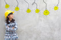Girl in yellow helmet with light bulb ideas Royalty Free Stock Photo