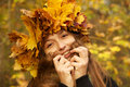 Girl in yellow leaves crown plays with her long hairs Royalty Free Stock Photos