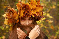 Girl in yellow leaves crown plays with her long hairs Stock Image