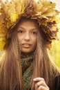 Girl in yellow leaves crown plays with her long hairs Stock Photo