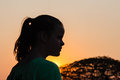 Girl young sunset silhouette watches sun setting going down silhouetted by colors of light Stock Photos