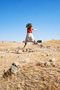 Girl and zorats karer monument in armenia jumping on carahunge plateau pre history megalithic Stock Photography