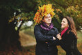 Girlfriend embracing her boyfriend he is got a corona of autumn leaves Royalty Free Stock Images