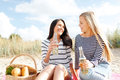 Girlfriends with bottles of beer on the beach Stock Photos