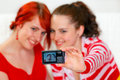 Girlfriends taking own photo. Focus on photocamera Royalty Free Stock Photos