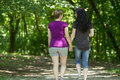 Girlfriends taking a walk through the park horizontal two women and holding hands Stock Image