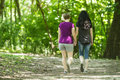 Girlfriends taking a walk through the park horizontal two women and holding hands Royalty Free Stock Photography