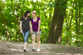 Girlfriends taking a walk through the park horizontal two women and holding hands Stock Images