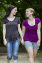 Girlfriends taking a walk through the park vertical two women and holding hands Royalty Free Stock Photos