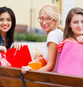 Girlfriends together out in city blond and brunette happy for a shopping with lots of shopping bags Stock Images