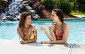 Girlfriends on vacation at swimmingpool beautiful happy smiling having fun drinking martini resort Royalty Free Stock Photo
