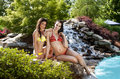 Girlfriends on vacation at swimmingpool beautiful happy smiling sitting in front of waterfall resort Royalty Free Stock Photos
