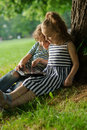 Girlie with boy sit under a tree having nestled and play on the tablet of years children are very keen they inreresy look at Stock Image