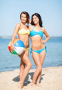 Girls with ball on the beach summer holidays vacation and activities in bikinis Stock Photos