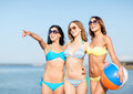 Girls with ball on the beach summer holidays vacation and activities in bikinis Stock Photo