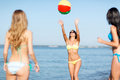 Girls with ball on the beach summer holidays vacation and activities concept in bikinies playing Royalty Free Stock Image